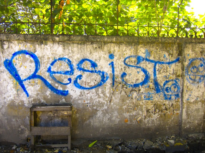 blue graffiti on a faded gray wall that sas resist
